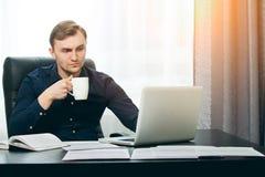 Redacteur die nieuw artikel controleren op zijn laptop met omhoog wenkbrauw royalty-vrije stock fotografie