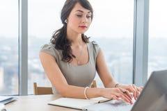 Redactor de anuncios femenino hermoso que se sienta en la oficina, nuevo artículo que mecanografía, trabajando con el texto, usan foto de archivo libre de regalías