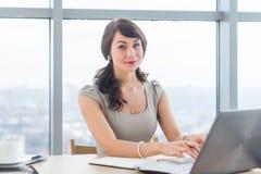 Redactor de anuncios femenino hermoso que se sienta en la oficina, nuevo artículo que mecanografía, trabajando con el texto, usan fotos de archivo