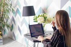 Redactor de anuncios de la mujer joven que trabaja en sitio web vía el ordenador portátil que se sienta en el interior casero foto de archivo libre de regalías