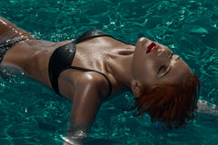 Redahead model laying on water in pool Royalty Free Stock Image