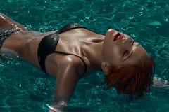 Redaheadmodel die op water in pool leggen Royalty-vrije Stock Afbeelding
