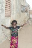 Redakcyjny podpis: THIAROYE, SENEGAL, AFRYKA †'†'LIPIEC 28, 2014 Niezidentyfikowana dziewczyna bawić się z skok arkaną w ulic Obraz Stock
