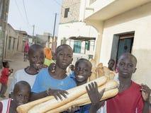 Redakcyjny podpis: Thiaroye, Senegal, Afryka †'Lipiec 28, 2014: Niezidentyfikowani dzieci w ulicie (chlebowe doręczeniowe chłop Fotografia Royalty Free