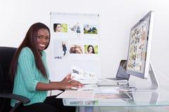 Redaktör som använder den digitala minnestavlan på fotobyrån Royaltyfri Fotografi