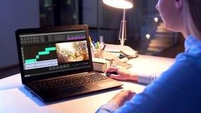 Redaktör som arbetar på videomapp på bärbara datorn på natten lager videofilmer