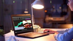Redaktör som arbetar på videomapp på bärbara datorn på natten arkivfilmer