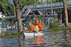 Redaktörs- foto av två buddistiska munkar som svävar i ett fartyg på en översvämmad gata i Bangkok i 2011 Arkivbilder