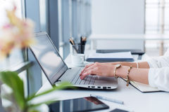 Redator fêmea em seu local de trabalho, casa, escrevendo o texto novo usando o portátil e a conexão a Internet de Wi-Fi na manhã fotos de stock royalty free