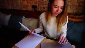 Redator fêmea que trabalha com papéis e portátil no café vídeos de arquivo