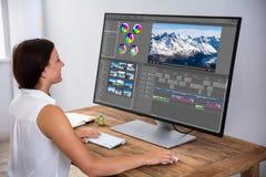 Redattore che pubblica video sul computer immagine stock