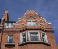 A redbricked house and the blue skies. This image shows a redbrick house in London. There`s a blue sky visible in the background Stock Photos