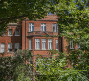 A redbricked house and green trees. This image shows a redbrick house in London. There are some green trees framing the image Stock Images