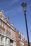 Redbricked houses, blue skies and a lamp post. Stock Photos