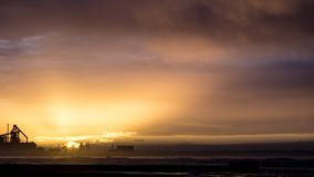 Redcar beach at sunset. Industrial background. stock photos