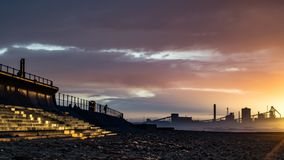 Redcar beach at sunset. Industrial background. stock photography