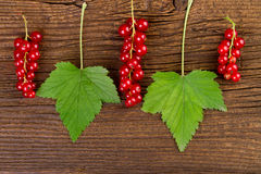Redcurrant berries with green leaves over old wooden background Stock Photography