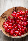 Redcurrant on a branch close to a wooden bowl. Stock Photo