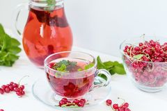 Redcurrant drink in transparent glass carafe and cup Stock Photos