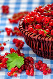 Redcurrant w łozinowym pucharze na stole Fotografia Stock