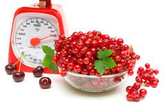 Redcurrants, kitchen scales and cherries on white background Royalty Free Stock Photography
