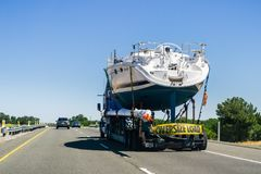 Boat transportation on the freeway. Redding / CA / USA - Truck carrying large boat on the interstate stock photo