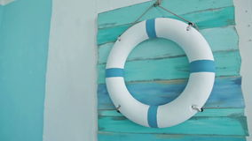 Reddingsboei aan boord op het die op blauwe muur hangen stock videobeelden