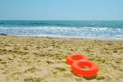 Reddingsboeien op een zandig strand Stock Afbeelding