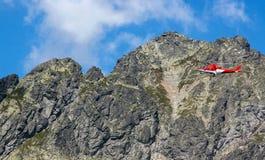 Reddingshelikopter die in de rotsachtige bergen vliegen stock afbeeldingen
