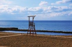 Reddingspost op strand op achtergrond van overzees met blauwe hemel Royalty-vrije Stock Foto