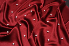 Reddish background. With pearls with foldings Royalty Free Stock Photos