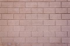 Reddish brown exterior concrete brick wall background. Background image of an exterior concrete brick wall in horizontal pattern. Weathered exterior concrete Stock Image