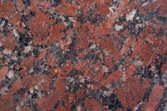 Reddish-brown granite texture with black and gray spots. Close up. Used as a background. Copy space for your text Stock Images