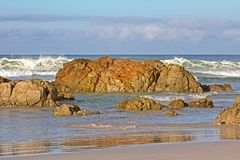 Reddish Brown Rocks on Beach. Reddish Brown Rocks with Waves Breaking in Background and Cloudy Sky Royalty Free Stock Photo