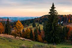 Reddish dawn in mountains. Beautiful autumn countryside. village near the forest in the distance stock image