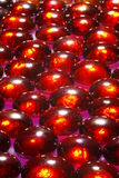 Reddish glass beads. A closeup of reddish glass beads, reflecting light brilliantly. They have been placed on a purple surface Stock Photos