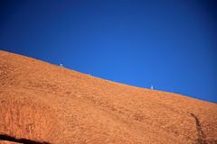 The reddish stone surface of Ayers Rock with two climbing ir. stock image