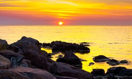 Reddish sunrise over the sea with rocky shore. Beautiful summer scenery and vacation concept stock images