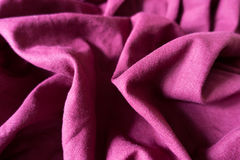 Reddish violet linen fabric with folds and shadows. Reddish violet plain linen fabric with folds and shadows Stock Photography