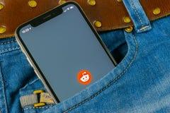 Reddit在苹果计算机iPhone x智能手机屏幕上的应用象在牛仔裤装在口袋里 Reddit app象 Reddit是网上社会媒介网 图库摄影