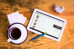 Reddit. Flat lay of tablet, cup of tea, pen and papers. Reddit is on the screen royalty free stock images