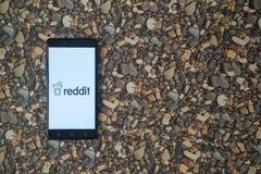 Reddit-Logo auf Smartphone auf Hintergrund von kleinen Steinen Stockfotografie