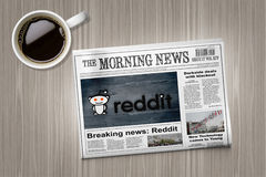 Reddit nyheterna i tidning på en tabell nära en kaffekopp Arkivbilder