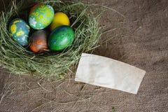 Rede av hö med påskägg och en anmärkning Arkivbild