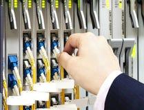 A rede de conexão da mulher cabografa aos interruptores na sala Fotografia de Stock Royalty Free