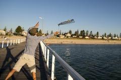Rede de jogo nova da cesta dos peixes e dos caranguejos do pescador atrativo feliz e orgulhoso no por do sol da doca do mar na pe Fotos de Stock Royalty Free