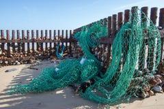 A rede de pesca do mar lavou acima na praia Poluição do oceano imagens de stock royalty free