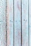 Rede de pesca em placas de madeira azuis rústicas velhas Imagem de Stock Royalty Free