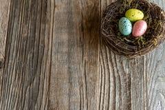 Rede med färgrika ägg på åldrigt trä royaltyfria bilder