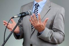 Rede mit Mikrofon und Handzeichen Lizenzfreie Stockfotos